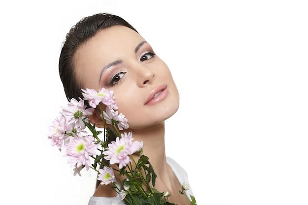 Schönheitsgesicht der jungen schönen frau mit den bunten blumen lokalisiert auf weiß