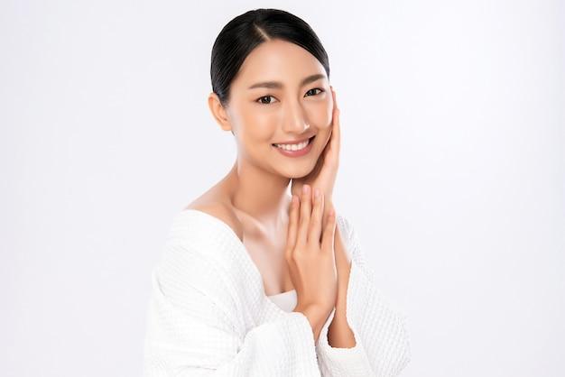 Schönheitsgesicht. lächelnde asiatische frau, die gesundes hautporträt berührt. schönes glückliches mädchenmodell mit frisch glühender hydratisierter gesichtshaut und natürlichem make-up auf weißer wand