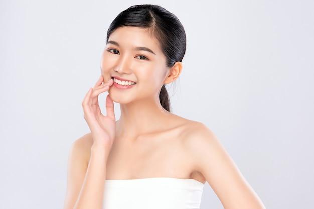 Schönheitsgesicht. lächelnde asiatische frau, die gesundes hautporträt berührt. schönes glückliches mädchenmodell mit frisch glühender hydratisierter gesichtshaut und natürlichem make-up,