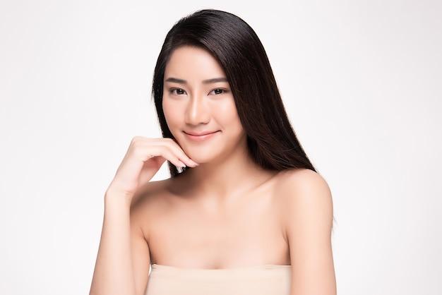 Schönheitsgesicht lächelnde asiatische frau, die gesundes hautporträt berührt schönes glückliches mädchenmodell mit frisch glühender hydratisierter gesichtshaut und natürlichem make-up