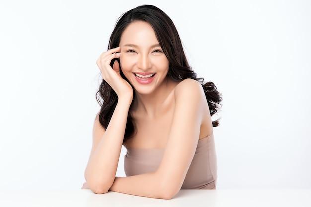 Schönheitsgesicht. lächelnde asiatische frau, die gesundes hautporträt berührt. schönes glückliches mädchenmodell mit frisch glühender hydratisierter gesichtshaut und natürlichem make-up