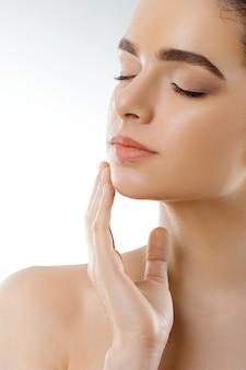 Schönheitsgesicht. schöne frau mit natürlichem make-up berühren eigenes gesicht. nahansicht. kosmetologie. hautpflege.