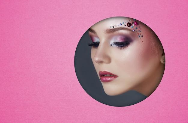 Schönheitsgesichtsmake-up einer jungen frau in einem runden loch des rosa papiers. frau mit schönem make-up, hellen augen, glühenden schatten und prallen lippen in einem kreisloch