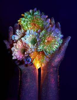 Schönheitshände einer frau im ultravioletten licht mit blumen in den handflächen. kosmetik für die handhautpflege