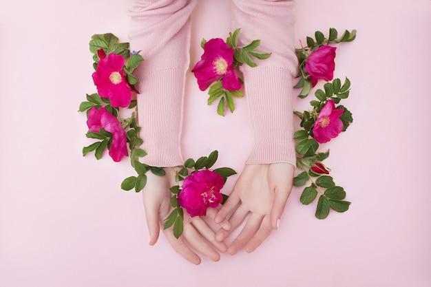 Schönheitshand einer frau mit roten blumen liegt auf tisch, rosa papierhintergrund.