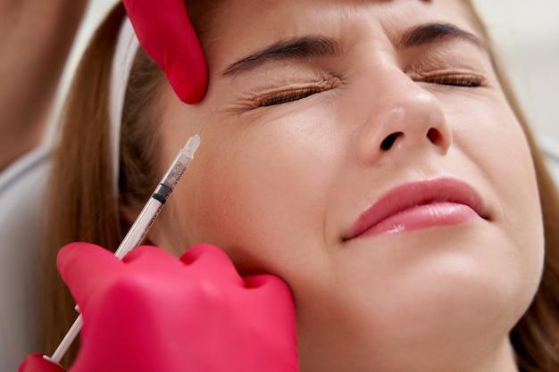 Schönheitsinjektionen in das junge weibliche gesicht glättung von mimikfalten durch biorevitalisierung