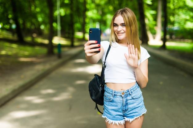 Schönheitsjugendliches mädchen, das ein selfie auf smartphone draußen im park am sonnigen tag nimmt.