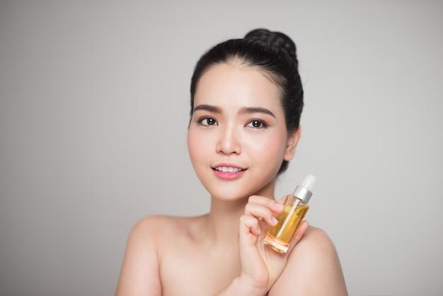 Schönheitskonzept. asiatische hübsche frau mit perfekter haut, die ölflasche hält