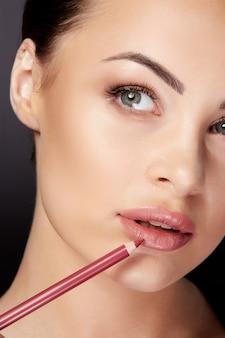Schönheitskonzept, halbes gesicht der frau, die make-up auflegt, lippen mit rotem lipliner malt. porträt der frau, die lippen mit bleistift berührt und beiseite schaut, studio, schwarzer hintergrund