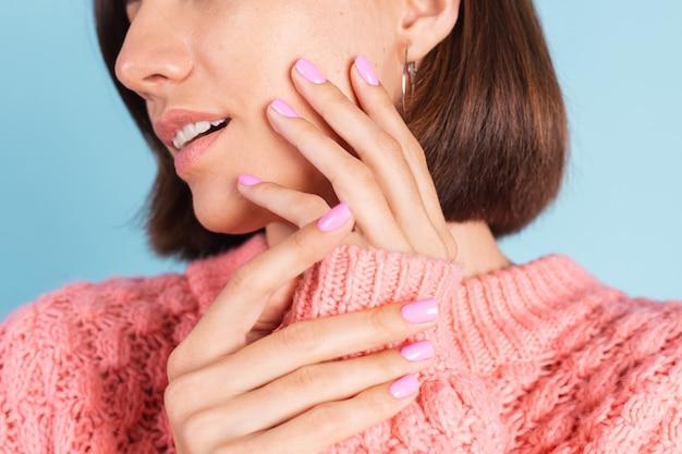 Schönheitskonzept, hübsche frau mit hellrosa nagelfarbenmaniküre an der wand