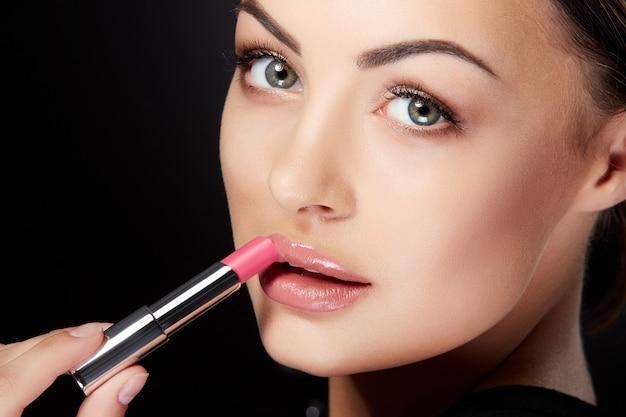 Schönheitskonzept, junge frau, die beiseite schaut und lippen mit rosenlippenstift malt. nahaufnahmeporträt des modells mit rosenlippen, studio mit schwarzem hintergrund