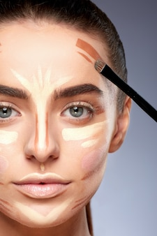 Schönheitskonzept. nahaufnahmeporträt der frau mit konturierung auf gesicht, make-up machend. arten des zeichnens make-up, frau, die kamera betrachtet, zeichnungslinie auf gesicht mit pinsel