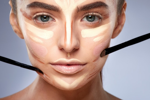 Schönheitskonzept. nahaufnahmeporträt der frau mit konturierung auf gesicht, make-up machend. arten von zeichnungs-make-up, frau mit nacktem make-up, die kamera betrachtet, bürsten nahe gesicht