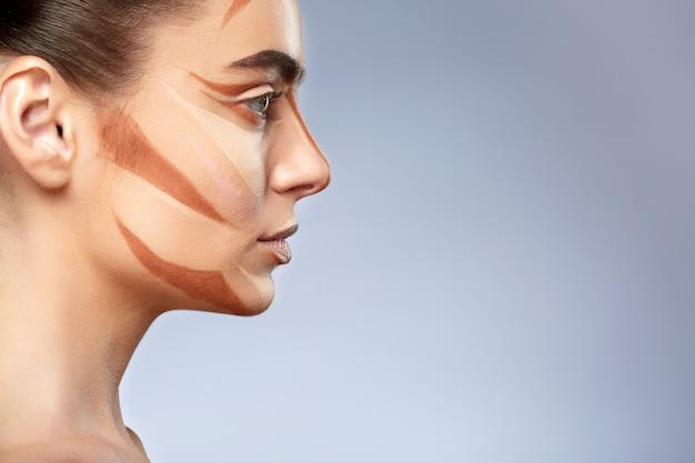 Schönheitskonzept. porträt der frau mit kontur auf gesicht. arten der zeichnung make-up, profil des mädchens mit nacktem make-up beiseite schauen