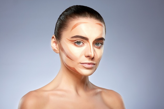 Schönheitskonzept. porträt der frau mit kontur auf gesicht. arten des zeichnens make-up, kopf und schultern des mädchens mit nacktem make-up, das kamera betrachtet