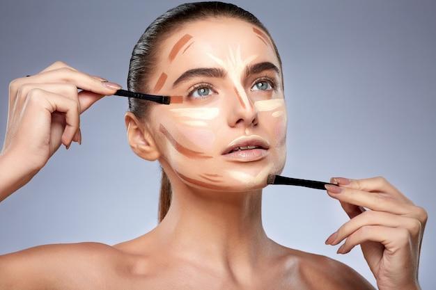 Schönheitskonzept. porträt der frau mit kontur auf gesicht, make-up machend. arten des zeichnens von make-up, frau mit nacktem make-up, die nach oben schaut und pinsel für make-up hält