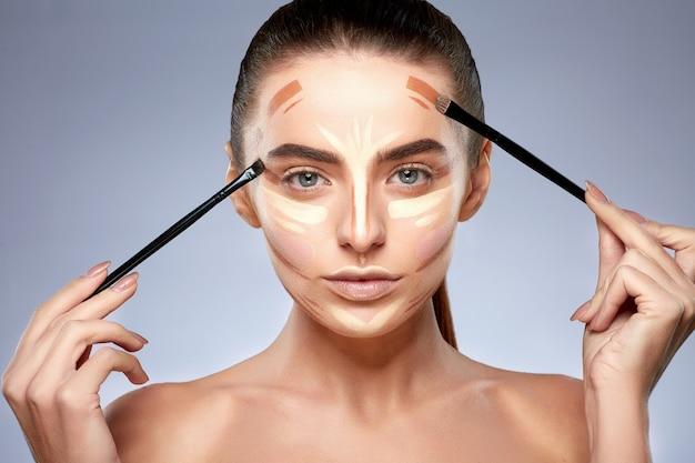 Schönheitskonzept. porträt der frau mit kontur auf gesicht, make-up machend. arten von make-up zeichnen, frau mit nacktem make-up in die kamera schauen, pinsel für make-up halten