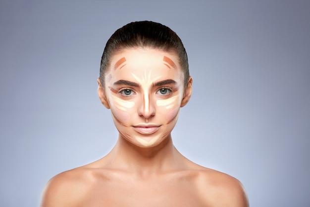 Schönheitskonzept. porträt der frau mit kontur im gesicht, basis für make-up. arten des zeichnens make-up, kopf und schultern des mädchens mit nacktem make-up, das kamera betrachtet