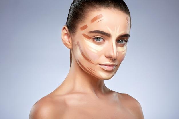 Schönheitskonzept. porträt der frau mit kontur im gesicht, basis für make-up. arten von zeichnung make-up, kopf und schultern der frau mit nacktem make-up mit blick auf die kamera
