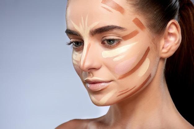 Schönheitskonzept. porträt der frau mit kontur im gesicht, basis für make-up. arten von zeichnungs-make-up, halbes profil der frau mit nacktem make-up, das nach unten schaut