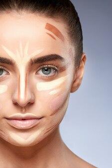Schönheitskonzept. porträt der frau mit kontur im gesicht, basis für make-up. arten von zeichnungs-make-up, nahaufnahme des mädchens mit nacktem make-up, das kamera betrachtet