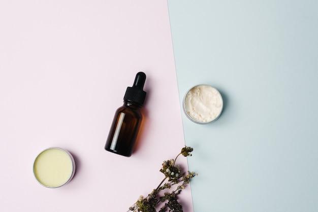 Schönheitskosmetik hautpflege creme serum hintergrund. produkte mit getrockneter blume, blätter auf tischansicht, flach gelegt. minimal modern. bernsteinfarbige flasche