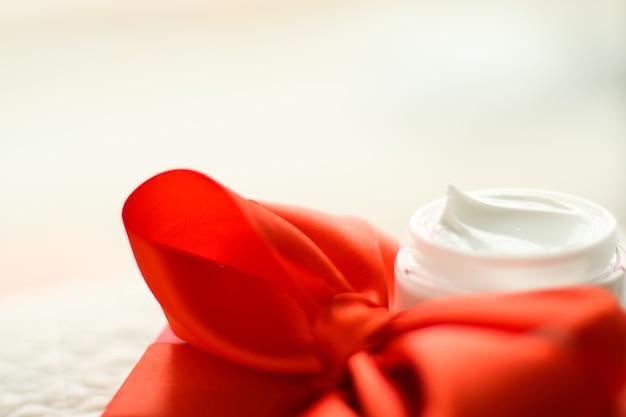 Schönheitskosmetik und hautpflegekonzept, luxus-gesichtscremedose und rote geschenkbox