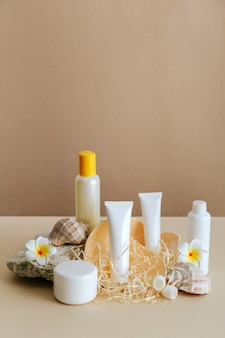 Schönheitskosmetikproduktzusammensetzung für hautpflege mit muschel auf beigefarbenem hintergrund des steinsockels. natürliches kosmetisches flaschenrohrmodell der creme mit tropischen blumen.