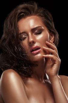 Schönheitsmädchen mit bronzefarbener hautfarbe und feuchter glänzender haut. nasses haar und saubere haut, rosa lippenstift auf den lippen, geschlossene augen und ein sexy foto.