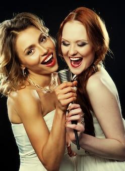 Schönheitsmädchen mit einem mikrofon singend und tanzend