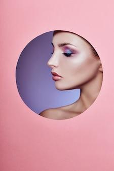 Schönheitsmake-upkosmetiknatur-modefrau in einem runden lochkreis im rosa papier, kopienraum
