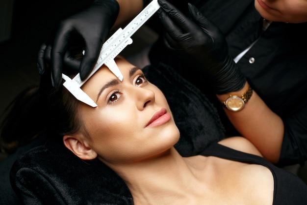 Schönheitsmeister, der augenbrauen mit bremssätteln vor dem puder-permanent-make-up misst. nahaufnahme