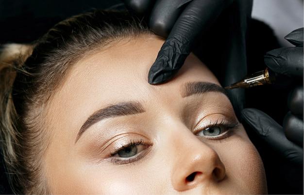Schönheitsmeister in handschuhen macht permanentes augenbrauen-make-up