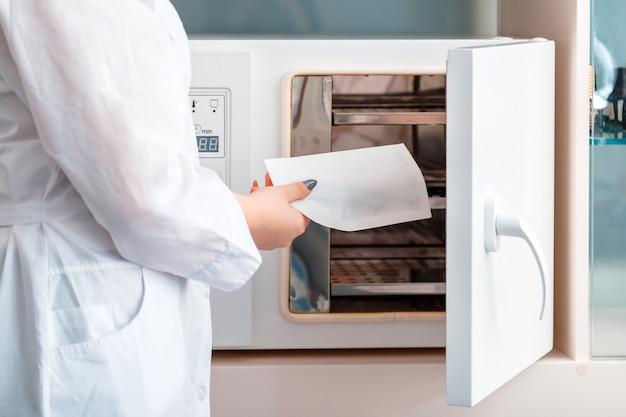 Schönheitsmeister legt maniküre-pediküre-instrumente werkzeuge zur reinigung in autoklaven sterilisationssysteme für desinfektionsscherenzangen in basteltasche. desinfektion von hygienemaschinen im schönheitssalon.