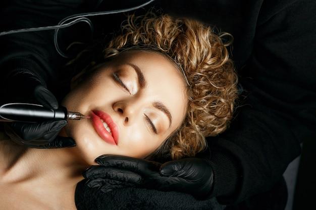 Schönheitsmeisterin in handschuhen, die einem entzückenden blonden model mit lockigem haar ein permanentes sputtern der lippen macht
