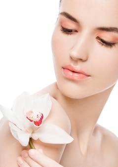 Schönheitsmode-modell, das weiße orchidee am badekurort hält