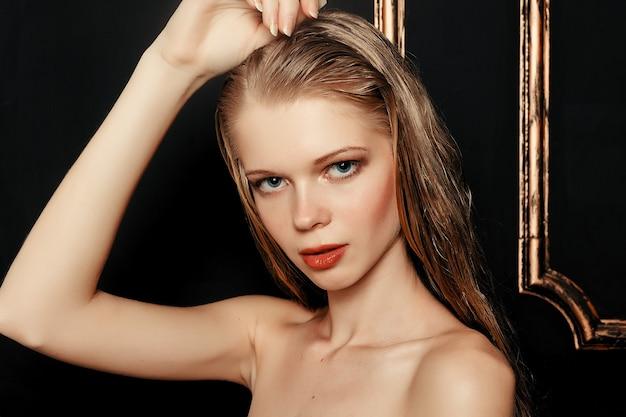 Schönheitsmode-modell-mädchen natürliches make-up nasses haar auf schwarzem goldhintergrund in warmen tönen. porträt der jungen frau mit mode-make-up