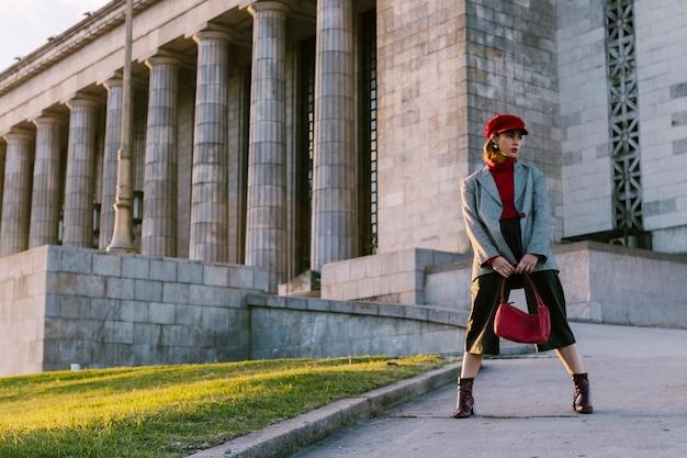 Schönheitsmode-modellfrau, die den stilvollen mantel in der hand hält handtasche trägt