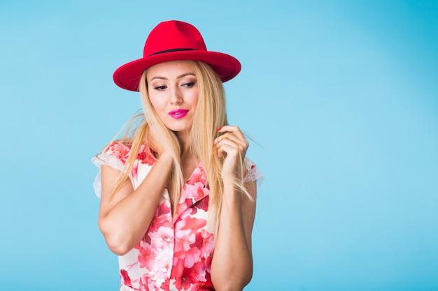 Schönheitsmode-sommerporträt der blonden frau mit roten lippen und rosa kleid auf blauer wand mit kopienraum.