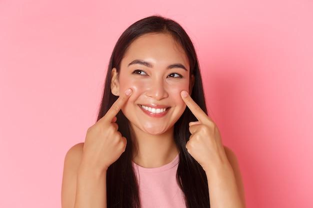 Schönheitsmode und lifestyle-konzept nahaufnahme von albernen und süßen entzückenden asiatischen mädchen, die ihre wangen stoßen...