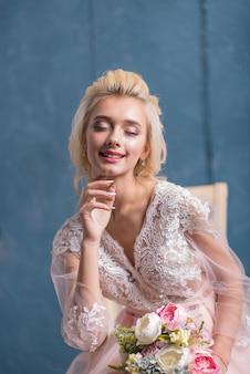Schönheitsmodebraut im winterdekor mit blumenstrauß in ihren händen. schöne braut porträt porträt make-up und frisur.