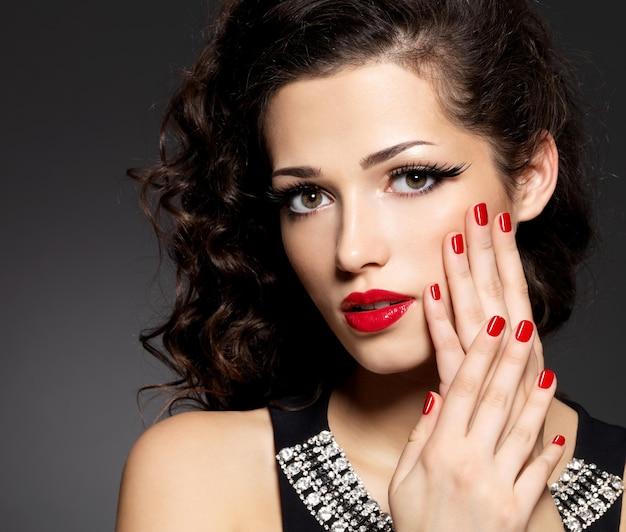 Schönheitsmodefrau mit roten nägeln, lippen und goldenem augen make-up - auf schwarzer wand
