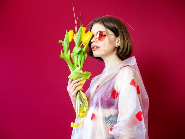 Schönheitsmodell woman im regenmantel mit frühlingsblumenstrauß. schönes mädchen mit einem blumenstrauß von gelben tulpenblumen. riechende blumen der glücklichen überraschten vorbildlichen frau. muttertagsgeschenk. valentinstag.