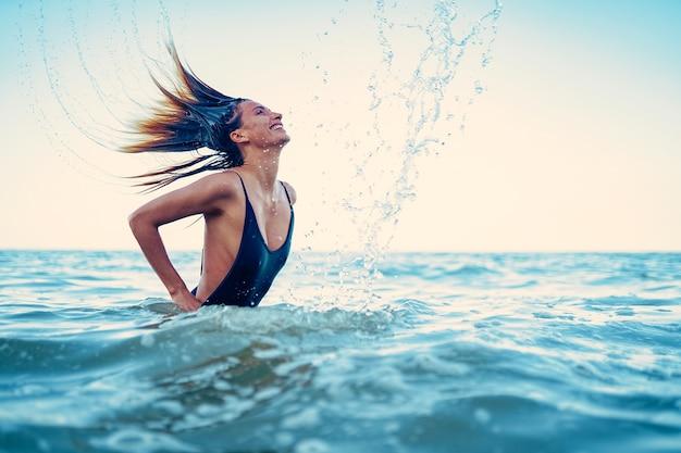Schönheitsmodellfrau, die wasser mit ihren haaren eine junge frau spritzt