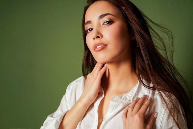 Schönheitsmodeporträt der sexy sinnlichen asiatischen jungen frau mit dem dunklen langen haar im weißen hemd auf grün
