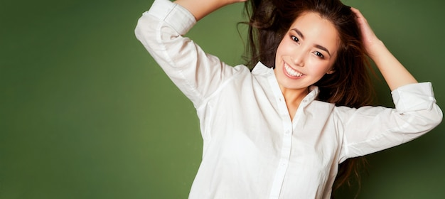 Schönheitsmodeporträt der sinnlichen lächelnden asiatischen jungen frau mit dem dunklen langen haar im weißen hemd auf grün
