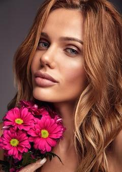 Schönheitsmodeporträt des jungen blonden frauenmodells mit natürlichem make-up und perfekter haut mit der hellen? rimson-chrysanthemenblumenaufstellung