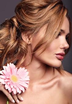 Schönheitsmodeporträt des jungen blonden frauenmodells mit natürlichem make-up und perfekter haut mit der hellen rosa gerberablumenaufstellung