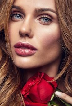 Schönheitsmodeporträt des jungen blonden frauenmodells mit natürlichem make-up und perfekter haut mit der schönen rosenaufstellung