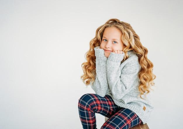 Schönheitsmodeporträt des lächelnden tweenmädchens des gelockten haares in den gemütlichen gestrickten strickjacken- und plaidhosen auf weiß lokalisiert